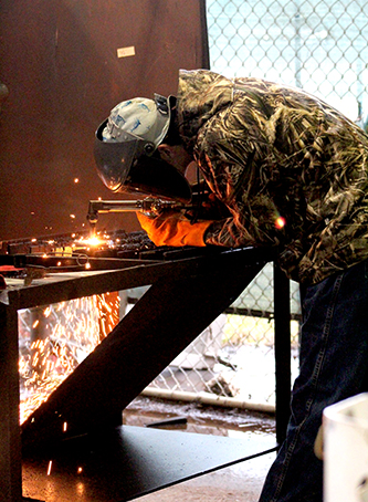 Junior, Kyle Canter welding two pieces of metal together.